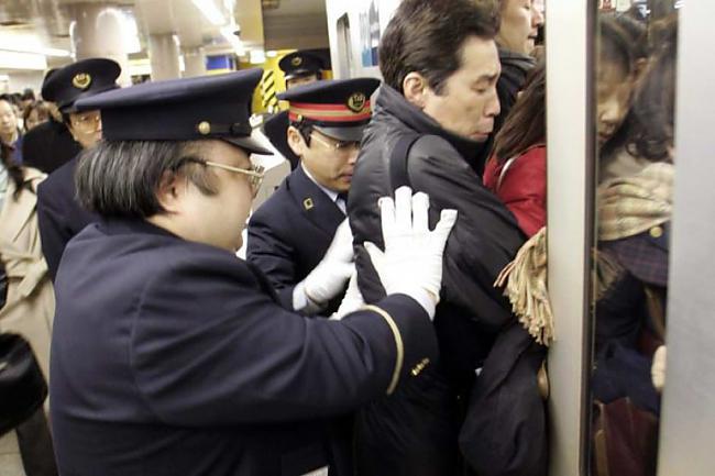 Stacijas darbinieki Japānā... Autors: Fosilija Pasaules pārpildītākie vilcieni tev liks iemīlēt Rīgas trolejbusus